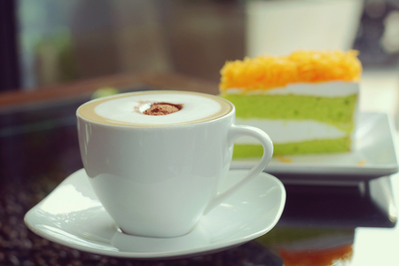 cosiness: Mocha in white coffee cup and Foythong Cake or Gold Egg Yolks Thread Cake in the Coffee Shop, vintage tone