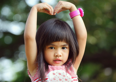 yo: Portrait children, Sa Rang Hae Yo, Little asian girl doing heart shape in the park Stock Photo
