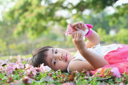 Portrait children, Little asian girl was lying on the grass in the park