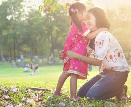 Asian family, Girls in cheongsam kissing her mather and laughing happily in park