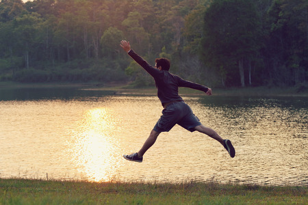 Jumps freedom, Asian man jumping on the river, during sunset, retro and vintage tone Stock Photo