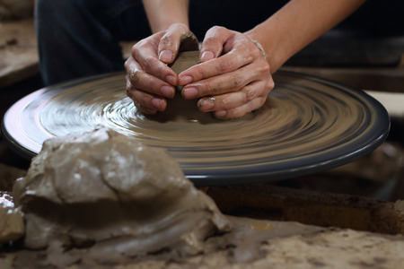 potter: potter making a clay pot in thailand