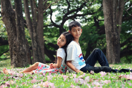 brethren: Portrait, asian children sitting on the grass in the park and look at camera Stock Photo