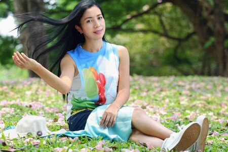 flick: Portrait of a beautiful asian woman flick heir and smiling sitting in the park Stock Photo