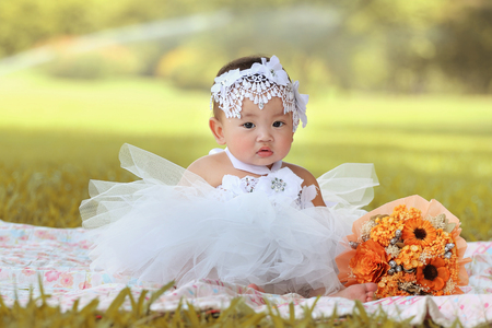 asian baby girl: Little asian girl wearing a white dress was playing happily and look at the camera in the park, close up Stock Photo