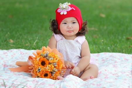 family portrait: Little asian girl wearing a red hat was playing happily and smiling in the park, close up Stock Photo