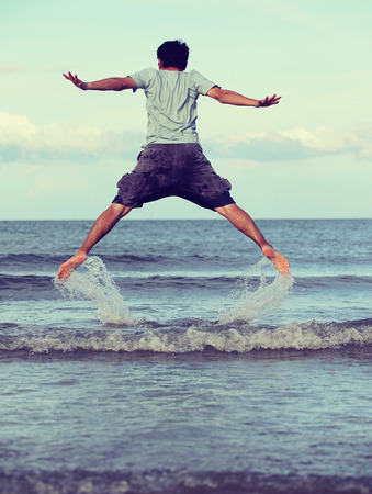 freedom: Jump to the freedom, Asian man jumping on the beach, retro and vintage tone
