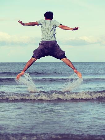 libertad: Saltar a la libertad, el hombre asiática que salta en la playa, retro época y el tono Foto de archivo