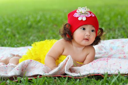 Little asian girl wearing a red hat was playing happily and smiling in the park, close up Stock Photo
