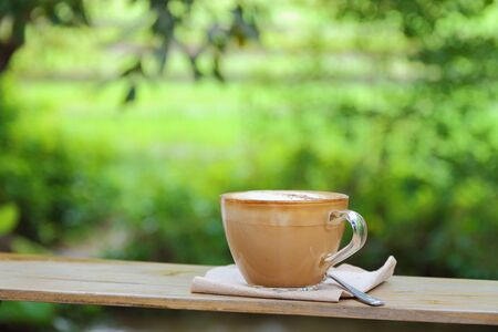cosiness: Hot coffee cup resting on a wooden board in nature.