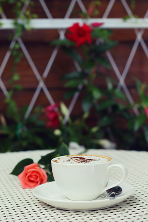 coffeetime: Hot coffee cup and rose on a white table. Stock Photo