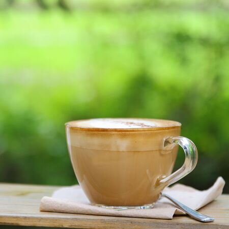coffeetime: Hot coffee cup resting on a wooden board in nature.