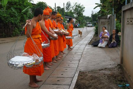 beliefs: Chiang Mai, Thailand - July 29, 2015: The old man was giving food to monk in the morning. Buddhist beliefs in Mae Chaem District, Chiang Mai, Northern Thailand.
