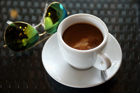 coffeetime: Hot coffee cup and sunglasses resting on a wooden board. Stock Photo