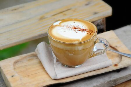 coffeetime: Hot coffee cup resting on a wooden board. Stock Photo