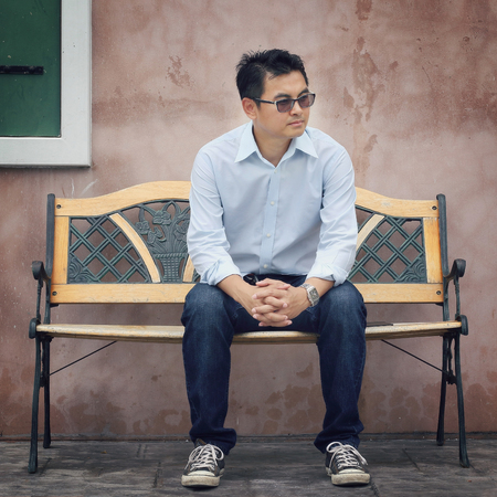 young male model: Asian Lifestyle, Asian man wearing glasses sitting on a chair and green window, vintage tone