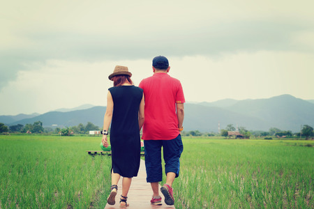 swain: Two lovers walking in the rice field and holding themselves by hands, vintage tone Stock Photo