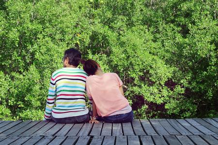 amantes: Dos amantes que se sientan en el puente en el bosque de mangle. Foto de archivo