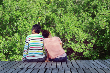 swain: Two lovers sitting on the bridge at the Mangrove forest.