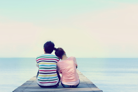 luna de miel: Dos amantes que se sientan en el puente en el mar.