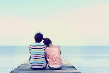 Twee geliefden zittend op de brug bij de zee. Stockfoto
