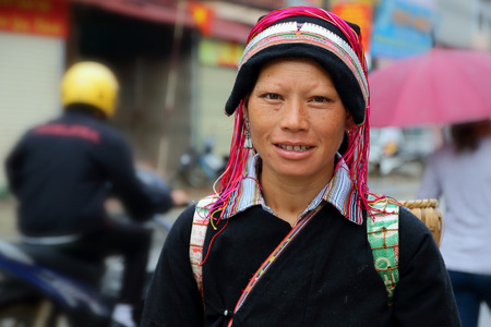 looked: Ha Giang, Vietnam - September 17, 2015: Hmong woman in Vietnam, She looked at the camera and smiling. In the northern province of Ha Giang in Vietnam. An area adjacent to China.
