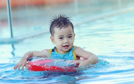 niños nadando: Niño asiático en el anillo de la nadada jugando en la piscina