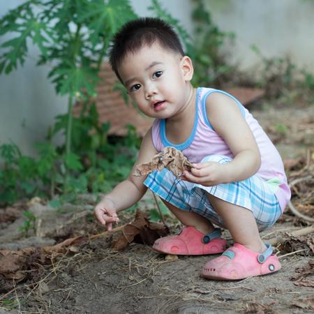 enfant qui joue: Vilain garçon jouant sur le terrain