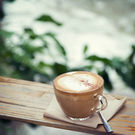 cosiness: Hot coffee cup resting on a wooden board in nature,  vintage tone
