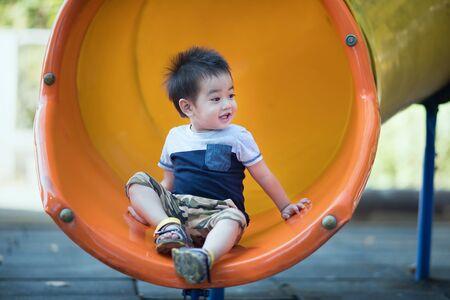 Asian boy laughing in amusement park Foto de archivo