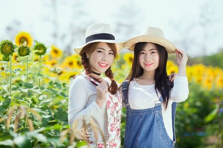 cute girl smiling: Outdoor portrait in the sunflowers garden, teenage asian girls wearing a hat.
