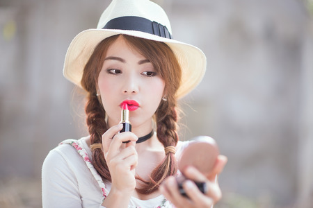 applying lipstick: portrait of teenage asian girl applying lipstick, focus on mouth. Stock Photo