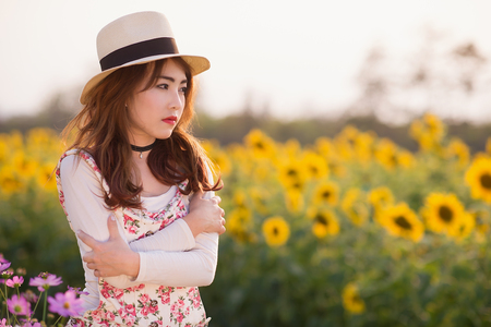 hugged: Outdoor portrait girl in the sunflowers garden, teenage asian girl wearing a hat and hugged herself in the evening