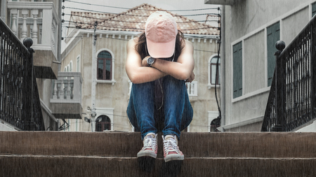 lovelorn: sad woman wearing a hat and hugging knees on stair in the rain Stock Photo