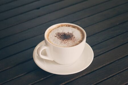 coffeetime: Cappuccino, Hot coffee cup on a wooden table, vintage tone and soft focus