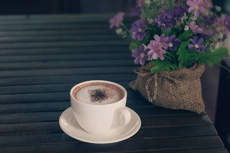 cosiness: Cappuccino, Hot coffee cup on a wooden table, vintage tone and soft focus