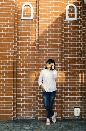 Asian woman in white shirt and jeans wearing sunglasses posing by the wall .