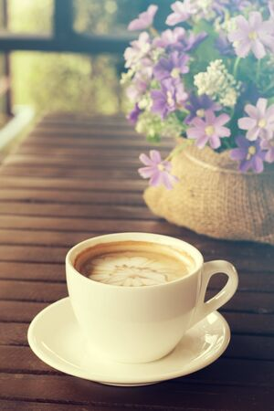 Cappuccino, Hot coffee cup on a wooden table, vintage tone and soft focus