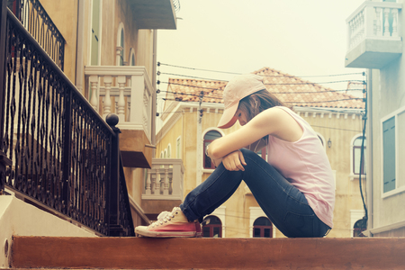 lovelorn: sad woman wearing a cap and hugging knees on stair, she is lonely most of the time, vintage tone