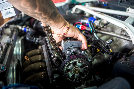 Mechanic checking the timing belt Editorial