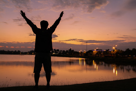 Silhouette of a man Happy successful  raising arms to the sky on lighting sunset Фото со стока