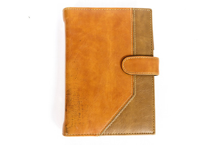 brown leather notebook cover and gold pen on white background photo