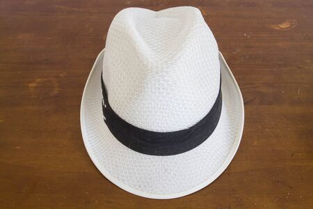 rawhide: White  hat with a hatband on a wooden table against dark background