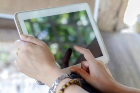 屋外でタブレットを使用しているアジア女性をクローズ アップの時間をリラックス