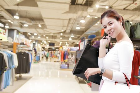 consumerism: happiness, consumerism, sale and people concept - smiling young woman asian with shopping bags over mallsuppermarket background