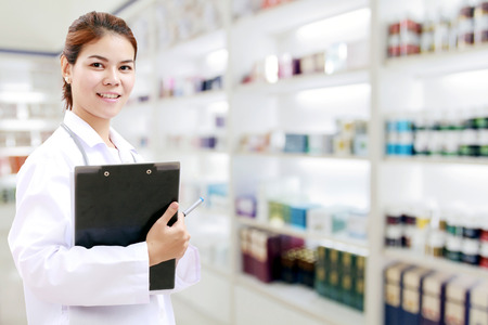 pharmacist chemist and medical doctor woman asia with stethoscope and clipboard checking medicine cabinet and pharmacy drugstore