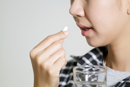 Asian women are taking medicines and vitamins for help Sick and healthy Фото со стока