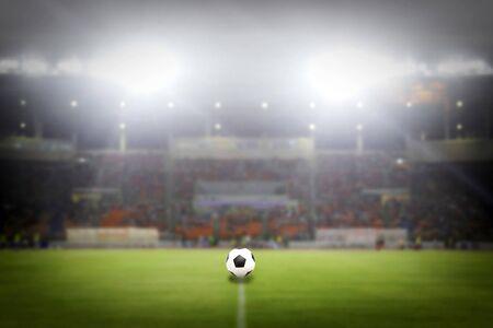 floodlit: Soccer Ball On Green Field of football stadium for background Stock Photo