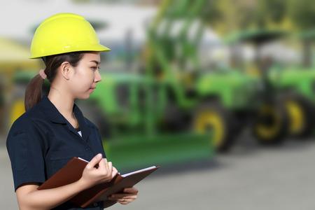 mecanico: Retrato de la sonrisa joven mec�nico de sexo femenino que revisa en un coche y de los tractores en el taller de reparaci�n de autom�viles