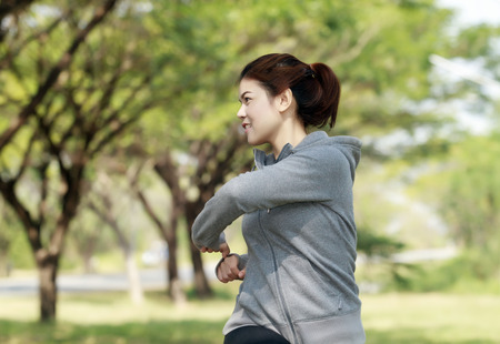 Athletic woman asia warming up and Young female athlete sitting on an exercising and stretching in a park before Runner outdoor on summer, healthy lifestyle concept